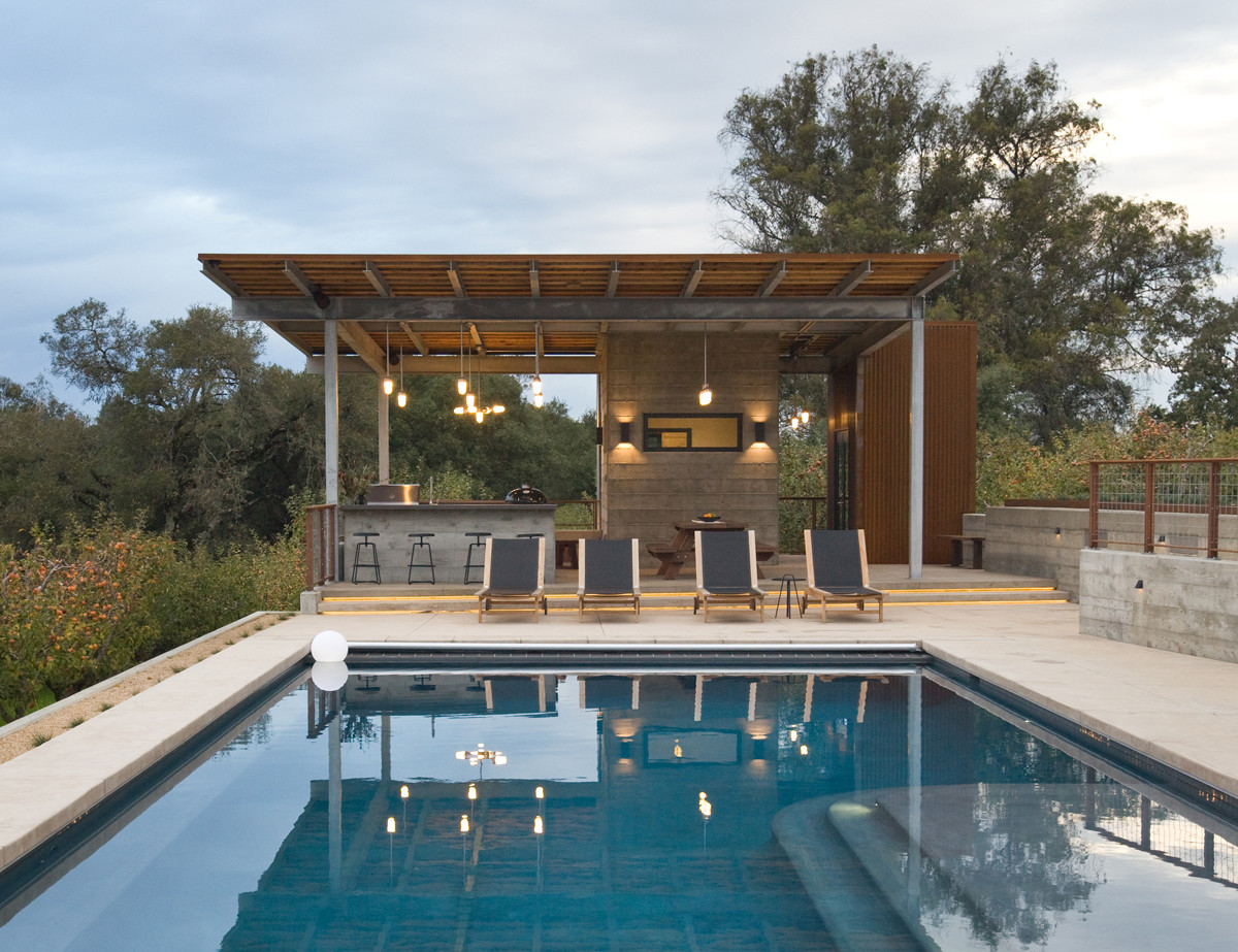 Outdoor Kitchen And Pool  modern outdoor kitchen overlooking swimming pool with